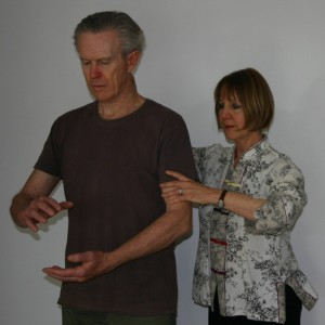 Penelope places her hands on a qigong student to correct posture