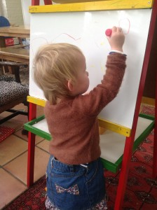 A small girl reaches up to draw on her whiteboard.