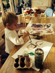A child concentrates as she paints a picture